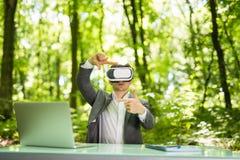 L'homme bel sûr d'affaires avec des verres de réalité virtuelle s'est dirigé avec des mains au bureau en parc vert Concept d'affa Photos stock