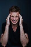 L'homme bel sent le mal de tête douloureux dans une chemise noire de v-cou sur a photo stock