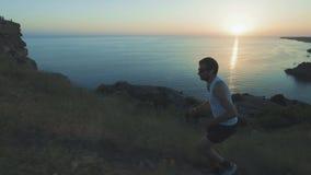 L'homme bel sportif fait des sports avec le téléphone et les écouteurs, fonctionnant le long de la côte au coucher du soleil tout banque de vidéos