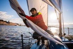 L'homme bel sur la voile blanche de contacts de yacht appelée le spinnaker asymétrique, travaille avec l'attirail en mer au jour  photo libre de droits