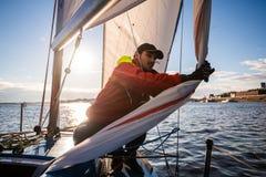 L'homme bel sur la voile blanche de contacts de yacht appelée le spinnaker asymétrique, travaille avec l'attirail en mer au jour  photos libres de droits