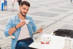 L'homme bel tient le comprimé tout en prenant la pause-café dans la ville image libre de droits
