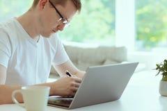 L'homme bel travaille à la maison avec son ordinateur portable photos libres de droits