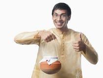 L'homme bengali portant un pot de rasgulla et montrant manie maladroitement vers le haut des sig Image stock