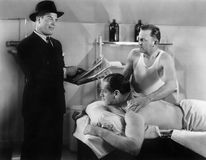 L'homme bien habillé lisant à un homme qui obtient un massage (toutes les personnes représentées ne sont pas plus long vivant et  Photographie stock libre de droits