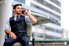 L'homme blanc d'affaires s'assied à la chaise et au téléphone portable d'utilisation pour appeler parmi la ville pendant le temps images stock