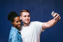L'homme blanc et la femme de couleur font le selfie, l'amusement et la joie Photographie stock