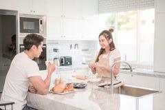 L'homme boit du café tandis qu'une femme prépare un repas photo stock
