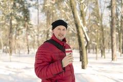L'homme boit du thé hors de la tasse Jeune homme de forêt d'hiver dans une veste chaude rouge avec le chapeau tricoté et l'écharp photos stock