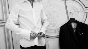 L'homme boutonne la chemise blanche image stock