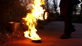 L'homme brûle deux grandes torches d'une flamme sur la terre extérieures la nuit dans le ralenti banque de vidéos