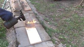 L'homme brûle le conseil avec un brûleur à gaz banque de vidéos