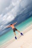 L'homme bronzé sautent dans les nageoires bleues sur la plage de sable Photographie stock