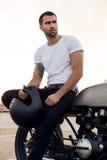 L'homme brutal s'asseyent sur la motocyclette de coutume de coureur de café photo stock