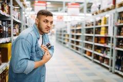 L'homme cache la bouteille d'alcool sous sa chemise photos stock