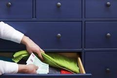 L'homme cache un salaire dans les euros dans un tiroir Image libre de droits