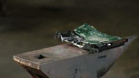 L'homme casse l'unité de disque dur avec un marteau lourd de traîneau, sur l'enclume Le plan rapproché de mouvement lent ont le b