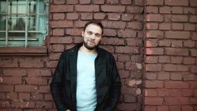 L'homme caucasien bel occasionnel sourit dans l'appareil-photo Mâle heureux réfléchi, veste en cuir, yeux bleus Mur de briques ro clips vidéos