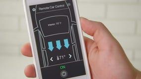L'homme change à distance la température dans sa voiture de voiture à télécommande utilisant l'interface fictive d'application de clips vidéos