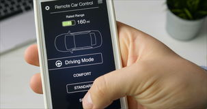 L'homme change conduire le mode de sa voiture à la voiture de mode de sport à télécommande utilisant l'interface fictive d'applic clips vidéos
