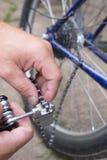 L'homme change la chaîne de bicyclette image libre de droits