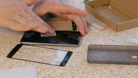 L'homme change les verres de sûreté criqués du téléphone portable le nouveau Essuie l'écran de téléphone avec un tissu Mains en g banque de vidéos
