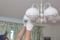 L'homme change une ampoule électrique, rendement énergétique images stock