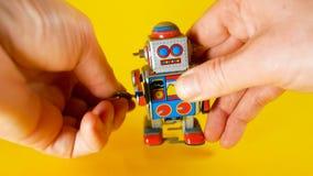 L'homme charge un robot en métal de cru pour l'inciter à marcher sur le fond jaune, idéal de longueur pour des sujets tels que l' photo libre de droits