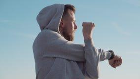 L'homme chauffe des muscles de ses mains dans le matin pour établir dehors banque de vidéos