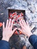 L'homme chauffe ses mains devant un feu ouvert Concept de camping avec les flammes ouvertes ext?rieures du feu Touriste chauffant photographie stock libre de droits