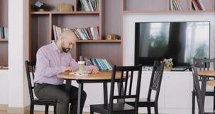 L'homme chauve barbu dans des vêtements de bureau lit un livre se reposant en café de hall d'hôtel avec la tasse de cappuccino banque de vidéos