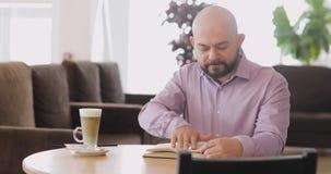 L'homme chauve barbu lit un livre se reposant en café de hall d'hôtel avec la tasse de cappuccino clips vidéos