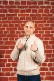 L'homme chauve dans le chandail blanc montre des pouces comme sur le fond de mur de briques Copiez l'espace photo stock
