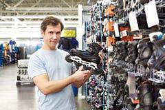 L'homme choisit des patins de rouleau dans la boutique de sports Images libres de droits