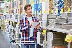 L'homme choisit des tuiles de mur pour la salle de bains dans le compagnon de bâtiment de supermarché photos stock