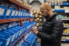 L'homme choisit en outils et matériaux de magasins de spécialités photo libre de droits