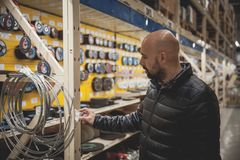 L'homme choisit en outils et matériaux de magasins de spécialités photos stock