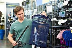 L'homme choisit la canne à pêche et le filet pour des poissons dans la boutique Image libre de droits