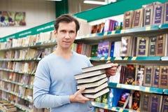 L'homme choisit le livre dans le magasin Image libre de droits