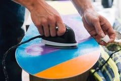 L'homme cire un surf des neiges Photographie stock libre de droits