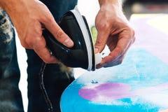 L'homme cire un surf des neiges Images libres de droits