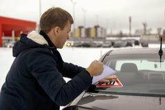 L'homme colle l'autocollant de signe d'épine sur la fenêtre de voiture photo libre de droits