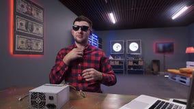 L'homme colle la MIC sans fil à la chemise ayant la boîte d'alimentation d'énergie avec le refroidisseur sur le bureau banque de vidéos