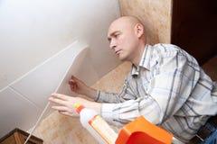 L'homme colle la tuile de plafond image stock