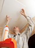 L'homme colle la tuile en plastique de plafond Photos libres de droits