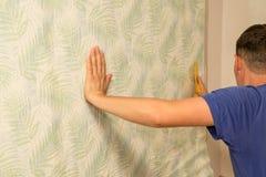 L'homme colle le papier peint au mur dans la maison image stock