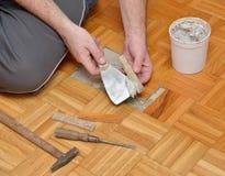 L'homme colle le plancher en bois image stock