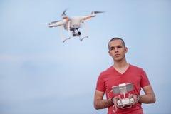 L'homme commande un quadrocopter Le foyer sélectif sur les hommes, bourdon est brouillé Images stock