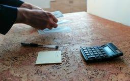 L'homme compte l'argent les étendant sur la table mains de plan rapproché Images libres de droits