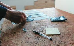 L'homme compte l'argent les étendant sur la table mains de plan rapproché Photo stock